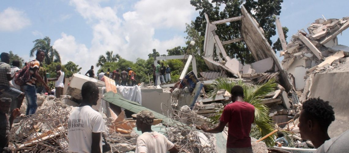 People search through the rubble of what used to be the Manguier Hotel after the earthquake hit on August 14, 2021 in Les Cayes, southwest Haiti. - Rescue workers scrambled to find survivors after a powerful 7.2-magnitude earthquake struck Haiti early Saturday, killing at least 304 and toppling buildings in the disaster-plagued Caribbean nation still recovering from a devastating 2010 quake. The epicenter of the shaking, which rattled homes and sent terrified locals scrambling for safety, was about 100 miles (160 kilometers) by road west of the center of the densely populated capital Port-au-Prince. (Photo by Stanley LOUIS / AFP)